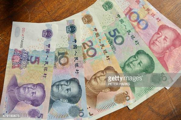 This photo illustration taken on March 17 2014 shows Chinese yuan bank notes in China's financial capital of Shanghai China's yuan traded weaker...