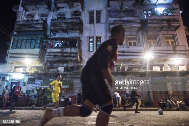 This photo is taken on February 9 2017 shows youth playing football on the street in downtown Yangon Once an Asian powerhouse Myanmar's football...
