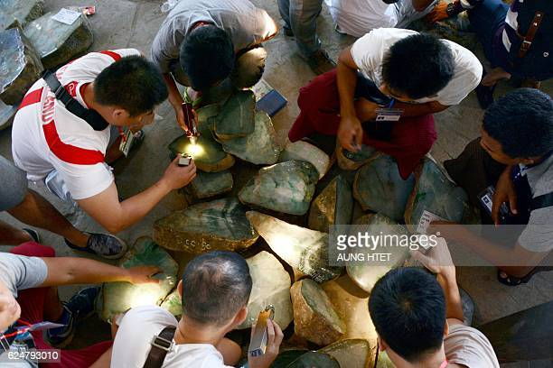 This photo is taken on November 20 2016 shows merchant checking jade stones on sale at the Mid Year Myanmar Jade and Gems Emporium 2016 in Naypyidaw...