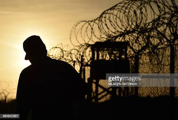 This photo made during an escorted visit and reviewed by the US military shows an US soldier walking next to the razor wiretopped fence at the...