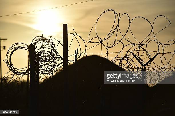 This photo made during an escorted visit and reviewed by the US military shows the razor wiretopped fence at the abandoned 'Camp XRay' detention...