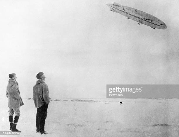 This photo one of the first to arrive shows captain Amundsen and Lincoln Ellsworth at King's Bay Spitzbergen watching the arrival of the Norge after...