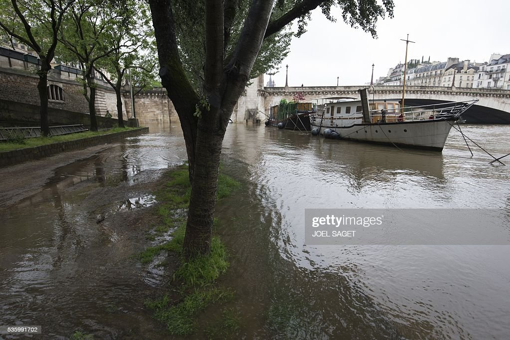 This photo shows a barge and a boat on the river Seine on Quai de la Tournelle after its banks became flooded following heavy rainfalls on May 31, 2016 in Paris. France's weather agency Meteo France maintained today 18 departments under orange alert for heavy rainfalls, which have already disrupted transports in the northeastern part of the country. / AFP / JOEL