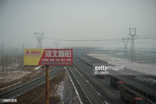 This photo shows a view of trucks driving past a billboard advertising a steel company from the window of a highspeed train during a journey...