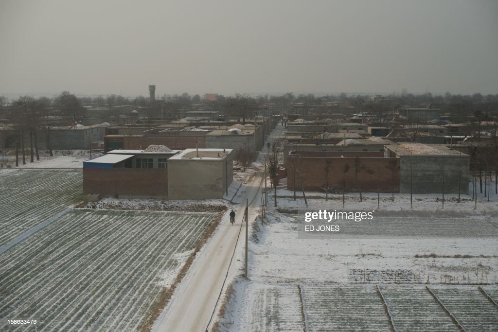 This photo shows a village from the window of a high-speed train during a journey organised for journalists to showcase a newly-built section of track through Hebei province, south of Beijing on December 22, 2012. China was showing off to the media the final link of the world's longest high-speed rail route, set to open on December 26, stretching from Beijing to the southern Chinese city of Guangzhou. Travelling at around 300 kph, trains on the new route are expected to cover the 2,298-kilometre (1,425-mile) journey in a third of the current time from 22 hours to eight. AFP PHOTO / Ed Jones