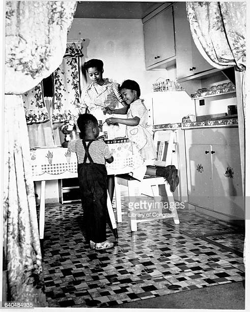 This photo shows an African American family enjoying themselves in one of the tenement buildings of Altgelt Gardens a housing project on Chicago's...