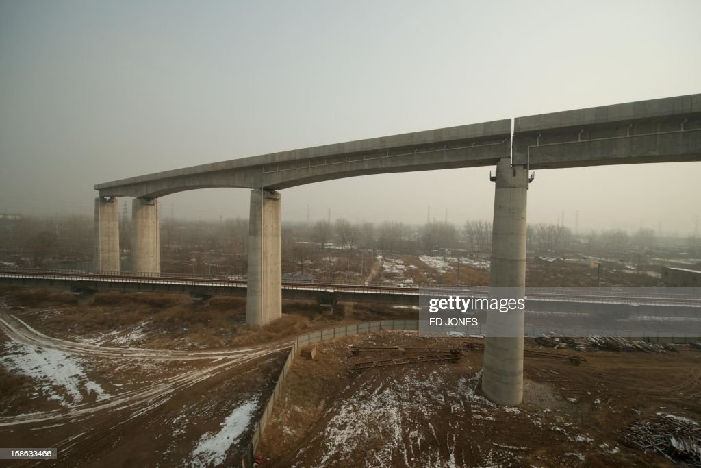 This photo shows an unfinished section of elevated railway from the window of a high-speed train during a journey organised for journalists to showcase a newly-built section of track through Hebei province, south of Beijing on December 22, 2012. China was showing off to the media the final link of the world's longest high-speed rail route, set to open on December 26, stretching from Beijing to the southern Chinese city of Guangzhou. Travelling at around 300 kph, trains on the new route are expected to cover the 2,298-kilometre (1,425-mile) journey in a third of the current time from 22 hours to eight. AFP PHOTO / Ed Jones