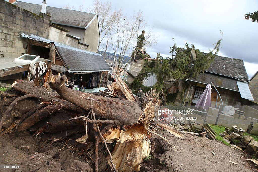 This photo shows an uprooted tree after it fell onto a house overnight on February 14, 2016 in Brive-la-Gaillarde, southwestern France, after a small tornado hit the town. About 15,000 homes were still without power Fabruary 14, including 3,000 in the Landes department and 3,000 in the Pyrenees-Atlantiques, after a storm raged through the southwest overnight. / AFP / DIARMID COURREGES