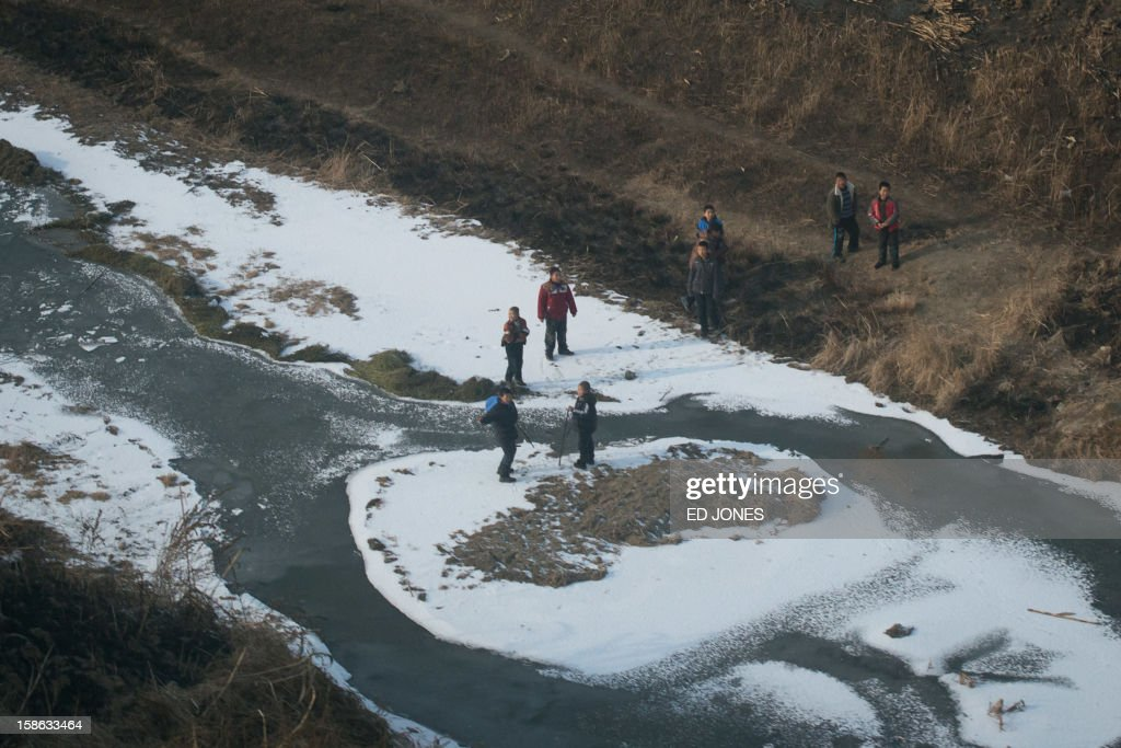 This photo shows children standing on a frozen river from the window of a high-speed train during a journey organised for journalists to showcase a newly-built section of track through Hebei province, south of Beijing on December 22, 2012. China was showing off to the media the final link of the world's longest high-speed rail route, set to open on December 26, stretching from Beijing to the southern Chinese city of Guangzhou. Travelling at around 300 kph, trains on the new route are expected to cover the 2,298-kilometre (1,425-mile) journey in a third of the current time from 22 hours to eight. AFP PHOTO / Ed Jones