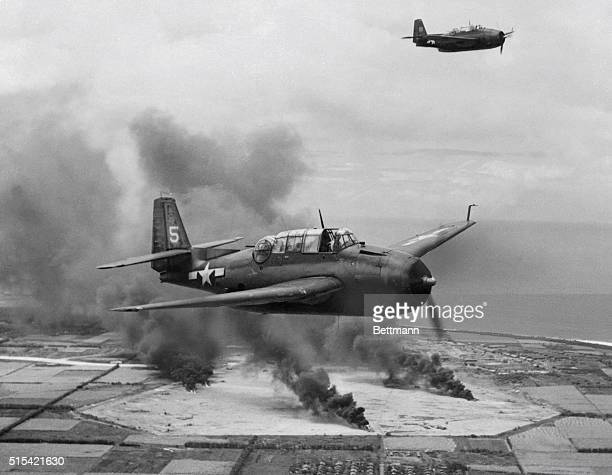 This photo shows huge pillars of smoke rise from direct hits on Japanese planes on Tinian Island Airfield as a result of attack by TBF Avengers in...