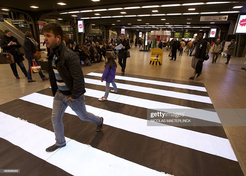 This photo shows people walking through a flashing zebra crossing, manufactured by IBM as part of their 'Smarter City Challenge', and being tested in a dedicated zone at Brussels' Midi railway station on March 27, 2014. AFP PHOTO / BELGA PHOTO / NICOLAS MAETERLINCK ** Belgium Out **