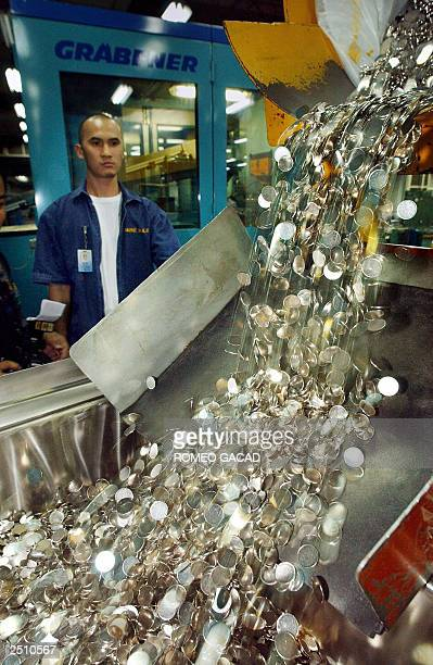 This photo taken 02 September 2003 shows a Central Bank employee monitoring unstamped coins as they are being poured into a stamping machine to be...