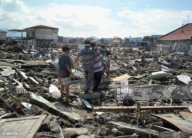 This photo taken 27 December 2004 shows local residents in Banda Aceh carrying away the body of a dead relative the day after a devastating 90...