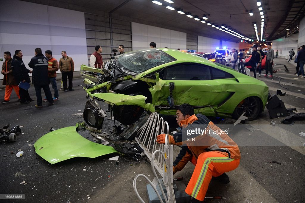 This photo taken early on April 12 2015 shows a badly damaged Lamborghini car and debris in a tunnel after a crash involving a Ferrari in Beijing The...