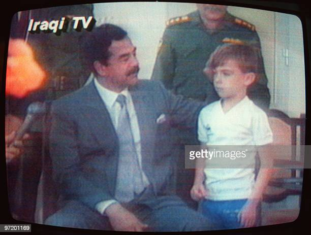 This photo taken from Iraqi TV shows Iraqi President Saddam Hussein patting Stuart Lockwood a young British boy on the head 23 August 1990 in Baghdad...