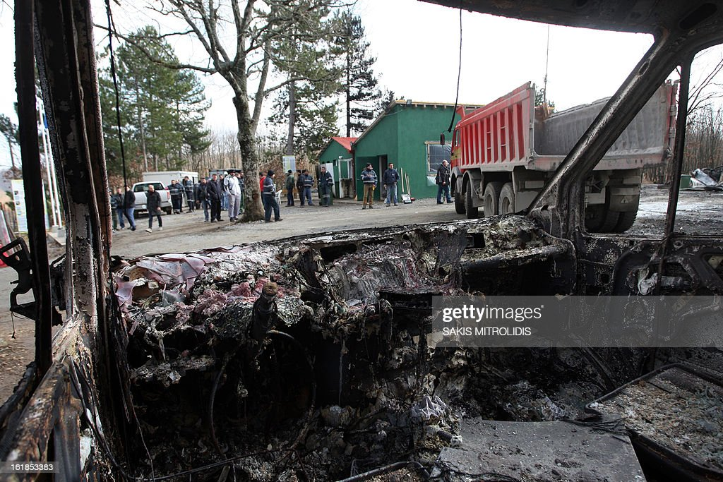 This photo taken from the inside of a bombed-out car shows workers of the Hellenic Gold company at the site of gold mining company in the forest of Skouries, some 620kms north of Athens, on February 17, 2013. Dozens of hooded men firebombed the premises of a Greek subsidiary of a Canadian gold mining company today, injuring a guard and damaging containers, cars and trucks. The site has faced opposition from citizens' groups who fear the project will cause irreversible harm to the local environment. They have been trying to halt the project since 2011, when the Greek government allowed Hellenic Gold, a subsidiary of Canadian company Eldorado Gold, to dig in the region. AFP PHOTO /Sakis Mitrolidis