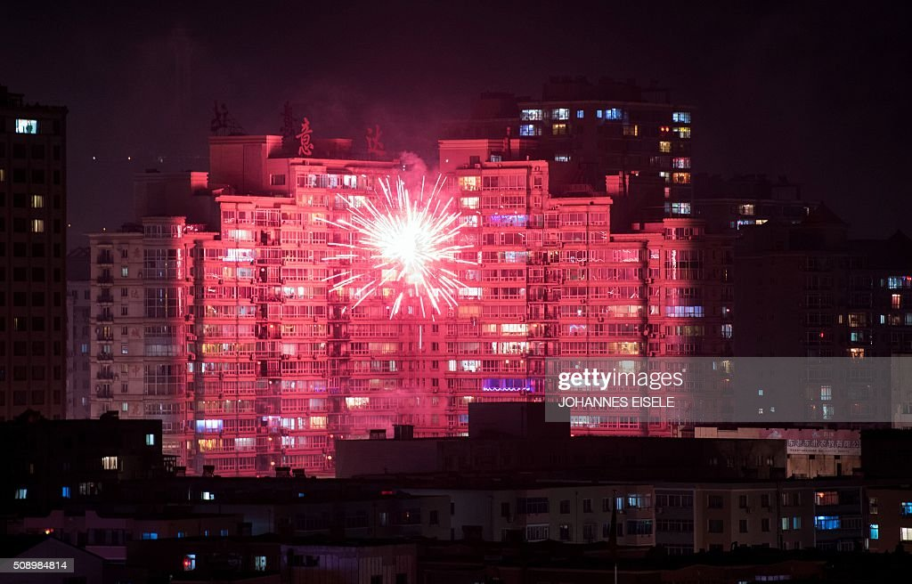 This photo taken late on February 7, 2016 shows fireworks illuminating buildings of the Chinese border town of Dandong, opposite to the North Korean town of Sinuiju, as people celebrate the eve of the Lunar New Year after North Korea said it had successfully put a satellite into orbit earlier in the day. The UN Security Council strongly condemned North Korea's rocket launch on February 7 and agreed to move quickly to impose new sanctions that will punish Pyongyang for 'these dangerous and serious violations.' With backing from China, Pyongyang's ally, the council again called for 'significant measures' during an emergency meeting held after North Korea said it had put a satellite into orbit with a rocket launch. AFP PHOTO / JOHANNES EISELE / AFP / JOHANNES EISELE