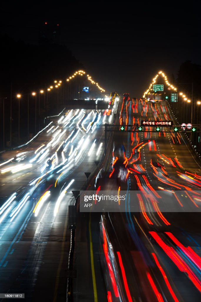 This photo taken late on September 17, 2013 shows a show shutter exposure of traffic departing from and arriving in Seoul over the Kyungbu highway ahead of 'Chuseok', South Korea's biggest holiday, which lasts from September 18 to 20. Approximately 35 million people were expected to travel to their hometowns and villages across the country to visit relatives this year, an increase of 4.9 percent compared with last year's holiday.