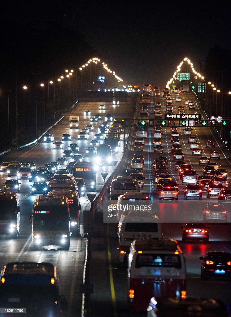 This photo taken late on September 17, 2013 shows traffic departing from and arriving in Seoul over the Kyungbu highway ahead of 'Chuseok', South Korea's biggest holiday, which lasts from September 18 to 20. Approximately 35 million people were expected to travel to their hometowns and villages across the country to visit relatives this year, an increase of 4.9 percent compared with last year's holiday. AFP PHOTO / KIM DOO-HO