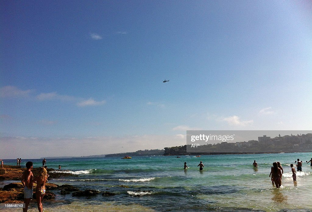 This photo taken on a smartphone shows swimmers at Sydney's iconic Bondi Beach standing on the edge of the waters after a shark alert forced thousands back to land on January 1, 2013. Thousands of bathers enjoying the hot New Year's Day weather on Australia's Bondi Beach fled the water on January 1 after a shark alert was sounded. AFP PHOTO / AMY COOPES
