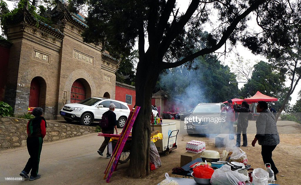 This photo taken on April 13, 2013 shows peddlers selling goods outside the Xingjiao Temple that holds relics of Xuan Zang, a Chinese monk who travelled to India to retrieve Buddhist scriptures in the 7th century, in Xian, central China's Shaanxi province. Authorities in Xian, the Chinese city home to the Terracotta Warriors, have ordered most of the buildings in a 1,300-year-old Buddhist temple demolished, staff said on April 11, provoking online outrage. CHINA OUT AFP PHOTO