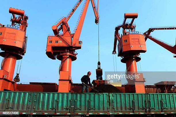 This photo taken on April 13 2015 shows a worker transporting iron ores on a truck in Qingdao port in QIngdao east China's Shandong province China...