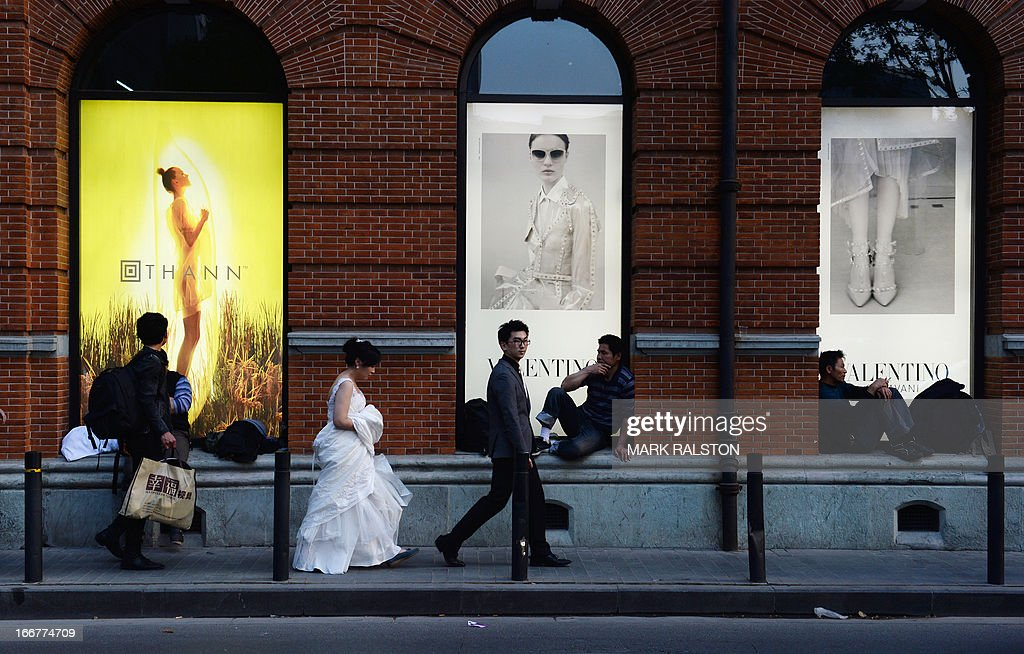 This photo taken on April 15, 2013 shows a wedding party walking past a recently renovated department store in the historic Bund area of Shanghai. China's economic growth slowed to 7.7 percent in the first quarter, data showed, below expectations and fuelling concerns that a recent recovery is faltering on subdued overseas demand. AFP PHOTO/Mark RALSTON