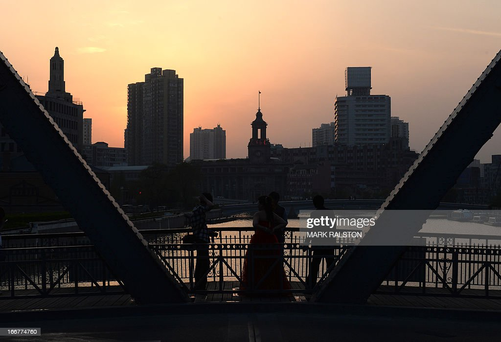 This photo taken on April 15, 2013 shows the sun setting over the historic Waibaidu Bridge in the Bund area of Shanghai. China's economic growth slowed to 7.7 percent in the first quarter, data showed, below expectations and fuelling concerns that a recent recovery is faltering on subdued overseas demand. AFP PHOTO/Mark RALSTON