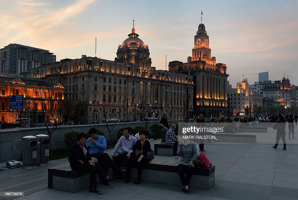 This photo taken on April 15, 2013 shows tourists in front of the old Hong Kong Bank building on the historic Bund of Shanghai. China's economic growth slowed to 7.7 percent in the first quarter, data showed, below expectations and fuelling concerns that a recent recovery is faltering on subdued overseas demand. AFP PHOTO/Mark RALSTON