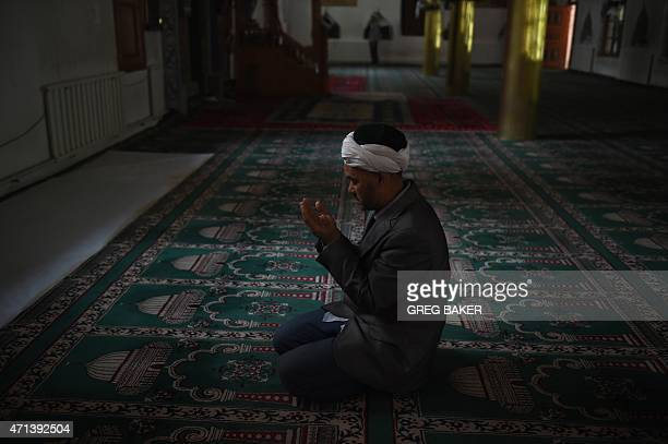 This photo taken on April 16 2015 shows a Uighur man praying in a mosque in Hotan in China's western Xinjiang region Chinese authorities have...