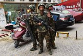 This photo taken on April 16 2015 shows paramilitary police officers standing guard outside a shopping mall in Hotan in China's western Xinjiang...