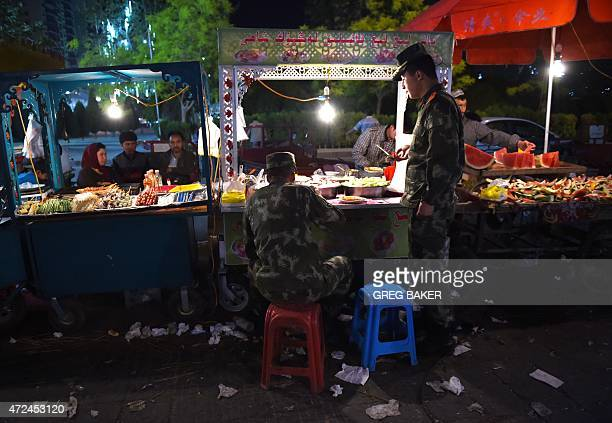 HAAS This photo taken on April 16 2015 shows two Han Chinese paramilitary policemen eating at a Uighur food stall at a night market after their shift...