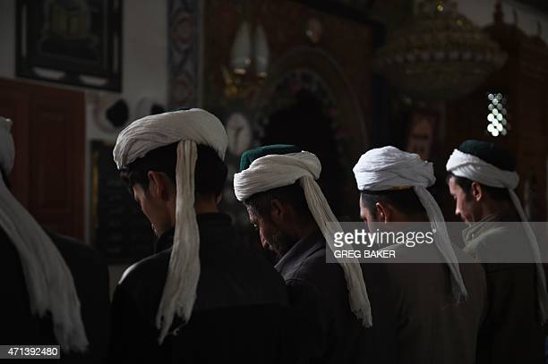 This photo taken on April 16 2015 shows Uighur men praying in a mosque in Hotan in China's western Xinjiang region Chinese authorities have...