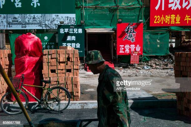 This photo taken on April 18 2017 shows a worker walking past renovation work on a street in Beijing It has become a familiar sight in China's...