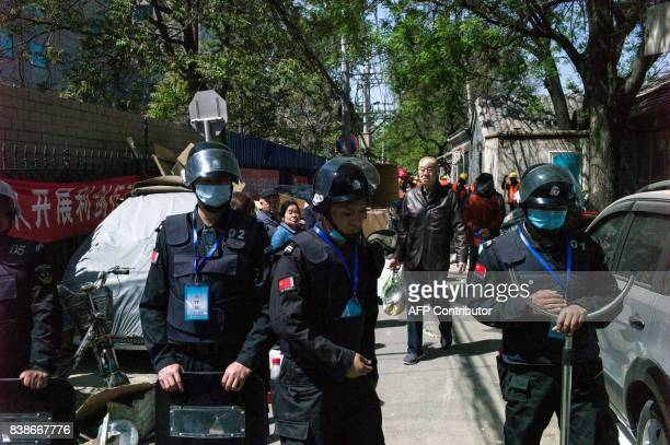 This photo taken on April 18 2017 shows Chinese security guards blocking the entrance of a street for pedestrians while workers brick up the...