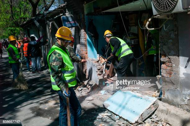 This photo taken on April 18 2017 shows Chinese workers blocking up the entrances to shops in Beijing It has become a familiar sight in China's...