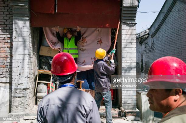 This photo taken on April 18 2017 shows Chinese workers blocking up the entrance to a shop in Beijing It has become a familiar sight in China's...