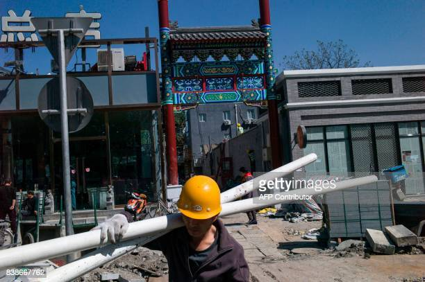 This photo taken on April 18 2017 shows Chinese workers renovating a street of restaurants in Beijing It has become a familiar sight in China's...