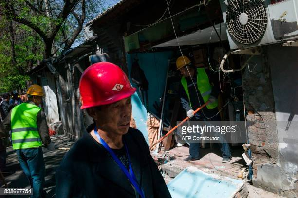 This photo taken on April 18 2017 shows Chinese workers starting to block up the entrance of shops in Beijing It has become a familiar sight in...