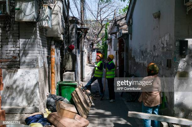 This photo taken on April 18 2017 shows Chinese workers surveying the building before they block up the entrance to establishments in Beijing It has...