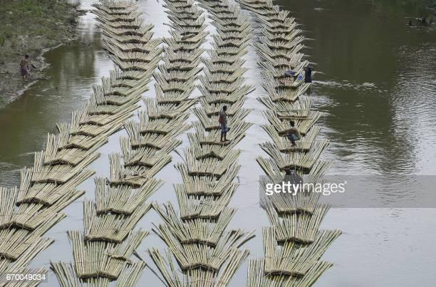 TOPSHOT This photo taken on April 18 2017 shows Indian labourers transporting bamboo logs down the Longai River near the TripuraMizoram state border...