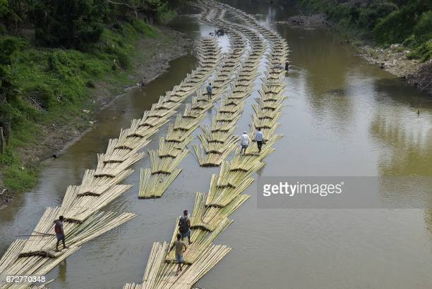 This photo taken on April 18 2017 shows Indian labourers transporting bamboo logs down the Longai River near the TripuraMizoram state border in...
