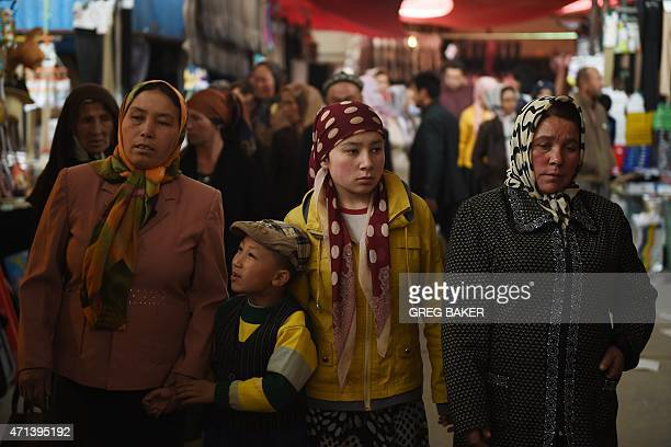 This photo taken on April 19 2015 shows a Uighur family at a bazaar in Kashgar in China's western Xinjiang region AFP PHOTO / Greg BAKER