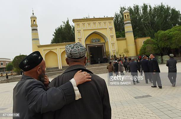 This photo taken on April 19 2015 shows Uighur men making their way to the Id Kah mosque for afternoon prayers in Kashgar in China's western Xinjiang...