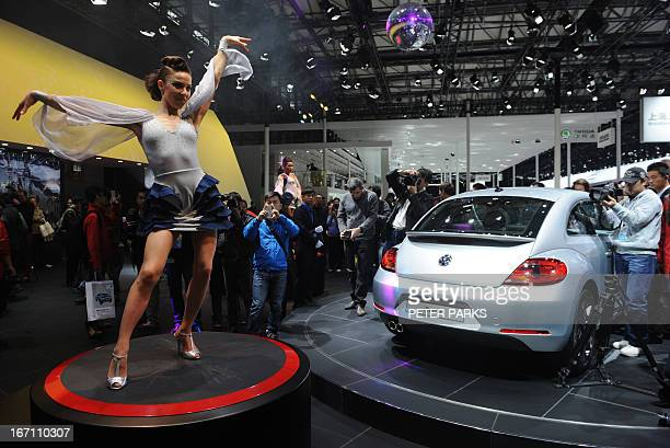 This photo taken on April 20 2013 shows a model dancing next to a VW Beetle on media day at the Shanghai auto show The Shanghai auto show which opens...