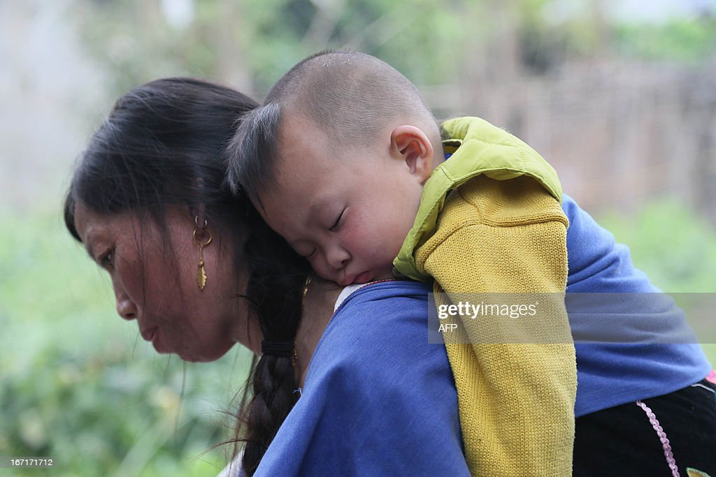 This photo taken on April 21, 2013 shows a child sleeping on a woman's back as she washes dishes in the temporary settlement in the disaster-hit area in Ya'an, southwest China's Sichuan province. Clogged roads, debris and landslides impeded rescuers on April 22 as they battled to find survivors of a powerful earthquake in mountainous southwest China that has left at least 188 dead. CHINA
