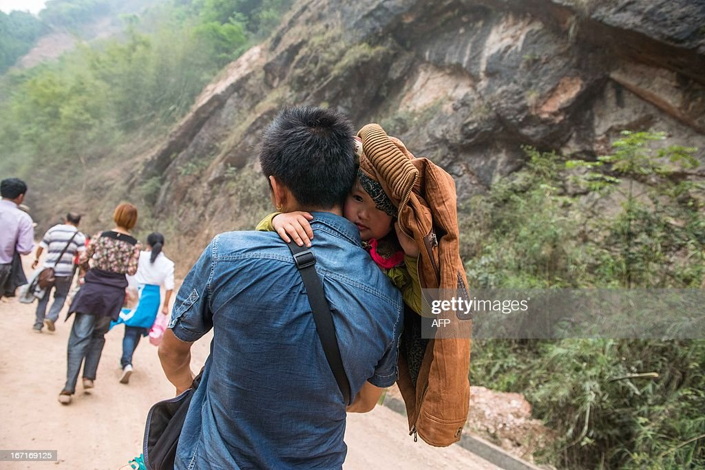 This photo taken on April 21, 2013 shows a man walking home with his daughter in the disaster-hit area in Ya'an, southwest China's Sichuan province. Clogged roads, debris and landslides impeded rescuers as they battled to find survivors of a powerful earthquake in mountainous southwest China that has left at least 188 dead. CHINA