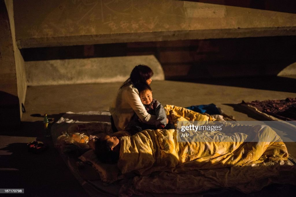 This photo taken on April 21, 2013 shows a mother hugging her child as others sleep in a temporary shelter in the disaster-hit area in Ya'an, southwest China's Sichuan province. Clogged roads, debris and landslides impeded rescuers as they battled to find survivors of a powerful earthquake in mountainous southwest China that has left at least 188 dead. CHINA