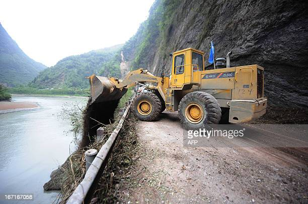 This photo taken on April 21 2013 shows an escavator cleaning the road to Baoxing county in the city of Ya'an southwest China's Sichuan province...