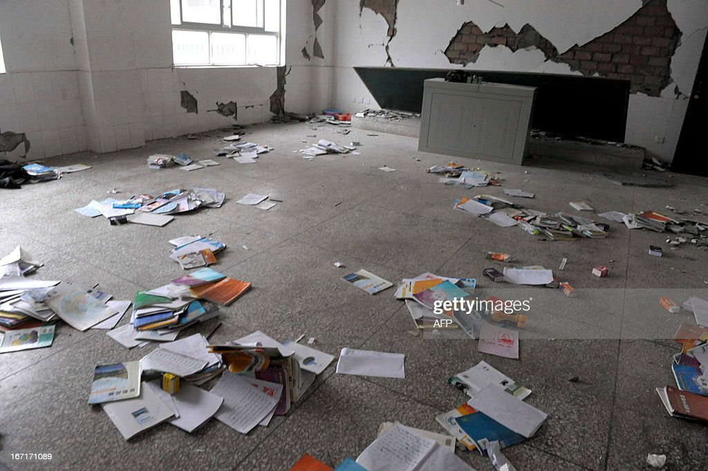 This photo taken on April 21, 2013 shows textbooks lying on the ground in a damaged classroom in disaster-hit Ya'an, southwest China's Sichuan province. Clogged roads, debris and landslides impeded rescuers as they battled to find survivors of a powerful earthquake in mountainous southwest China that has left at least 188 dead. CHINA OUT AFP PHOT